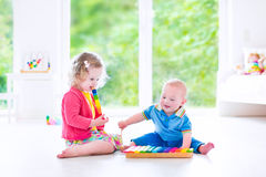 Kids playing music with xylophone. Two little children - cute curly toddler girl and a funny baby boy, brother and sister playing music, having fun with colorful stock photo