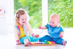 Kids playing music with xylophone. Two little children - cute curly toddler girl and a funny baby boy, brother and sister playing music, having fun with colorful