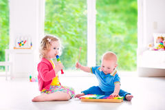 Kids playing music with xylophone. Two little children - cute curly toddler girl and a funny baby boy, brother and sister playing music, having fun with colorful royalty free stock photos