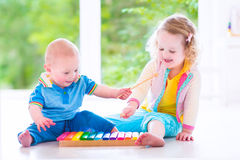 Kids playing music with xylophone. Two little children - cute curly toddler girl and a funny baby boy, brother and sister playing music, having fun with colorful stock images