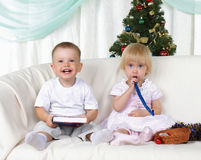Kids playing near to christmas fur-tree Stock Images