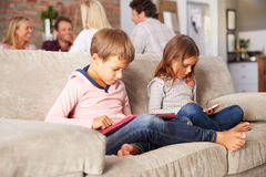 Kids playing with new technology while adults entertain stock photography