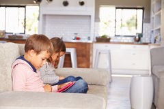 Kids playing with new technology while adults entertain Royalty Free Stock Photo