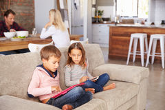 Kids playing with new technology while adults entertain Stock Image