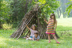 Kids playing next to wooden stick house Royalty Free Stock Photography