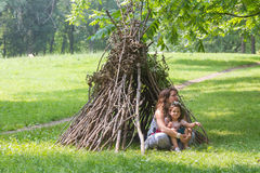 Kids playing next to wooden stick house looking like indian hut, Royalty Free Stock Photo