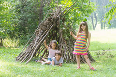Kids playing next to wooden stick house looking like indian hut,. Tepee Stock Image