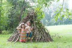 Kids playing next to wooden stick house looking like indian hut, Stock Images