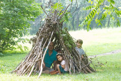Kids playing next to wooden stick house looking like indian hut, Stock Photo