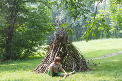 Kids playing next to wooden stick house looking like indian hut, Royalty Free Stock Images