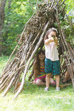 Kids playing next to wooden stick house looking like indian hut, Stock Photography