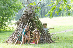 Kids playing next to wooden stick house looking like indian hut, Stock Image