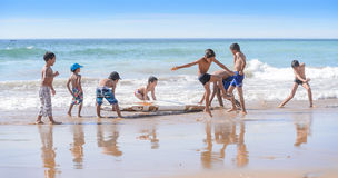 Kids playing with old surfboard,Taghazout surf village,agadir,morocco. A group of young local kids playing with an old surfboard in the shore break waves in Stock Images