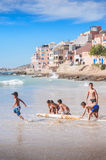 Kids playing with old surfboard,Taghazout surf village,agadir,morocco  2. A group of young local kids playing with an old surfboard in the shore break waves in Royalty Free Stock Photography