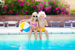 Kids playing at outdoor swimming pool. Little girl and boy play and swim in resort pool on tropical beach island summer family vacation. Swim and eye wear, sun Stock Photos