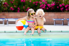 Kids playing at outdoor swimming pool. Little girl and boy play and swim in resort pool on tropical beach island summer family vacation. Swim and eye wear, sun Royalty Free Stock Photo
