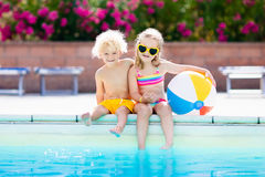Kids playing at outdoor swimming pool. Little girl and boy play and swim in resort pool on tropical beach island summer family vacation. Swim and eye wear, sun Stock Image
