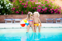 Kids playing at outdoor swimming pool. Little girl and boy play and swim in resort pool on tropical beach island summer family vacation. Swim and eye wear, sun Royalty Free Stock Photos