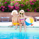 Kids playing at outdoor swimming pool. Little girl and boy play and swim in resort pool on tropical beach island summer family vacation. Swim and eye wear, sun Stock Photo