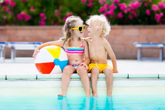 Kids playing at outdoor swimming pool. Little girl and boy play and swim in resort pool on tropical beach island summer family vacation. Swim and eye wear, sun Royalty Free Stock Photography