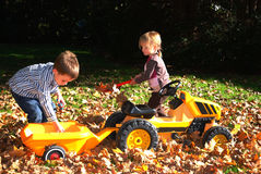 Kids playing outside. Happy siblings  playing outside in a pile of red and yellow fallen  leaves on  sunny autumn day Stock Image