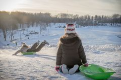 Kids playing outside with their sled on the snow. Two kids playing outside with thier sled on a cold winter day Stock Photo