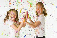 Kids playing with paint. Two young girls giving a high five while covered in colorful splattered paint.  Each has a happy expression and the playing appears to Royalty Free Stock Photography