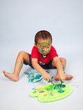 Kids playing with paint. Preschooler playing with paint and brush Stock Images