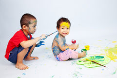 Kids playing with paint. Preschoolers playing with paint shot in studio Stock Image