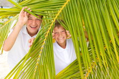 Kids playing in palm leaves Royalty Free Stock Photography