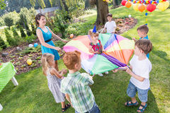 Kids playing parachute games. Kids and party entertainer playing parachute games in the garden Stock Image