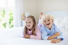 Kids in bed. Children in pajamas. Family bedroom. Stock Photography