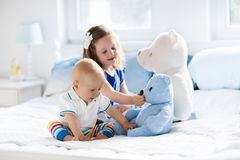 Kids playing on parents bed. Little girl and baby boy, brother and sister playing in parents bed. Family with children in the morning. Kids play in white bedroom Stock Photography