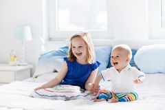 Kids playing on parents bed Stock Photography