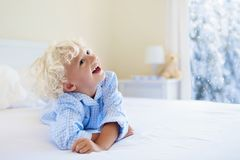 Kid in bed. Winter window. Child at home by snow. Stock Photography