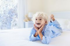 Kid in bed. Winter window. Child at home by snow. Stock Images