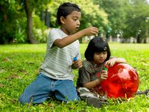 Kids playing in a park. Two asian kids playing in a park stock image