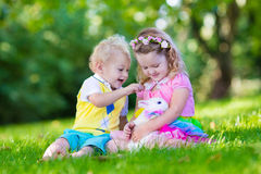 Kids playing with pet rabbit Royalty Free Stock Photos