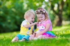 Kids playing with pet rabbit royalty free stock photos