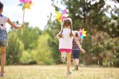 Kids playing with pinwheels Royalty Free Stock Image