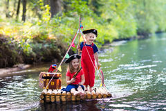 Kids playing pirate adventure on wooden raft Stock Photo