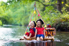 Kids playing pirate adventure on wooden raft. Kids dressed in pirate costumes and hats with treasure chest, spyglasses, and swords playing on wooden raft sailing Stock Image