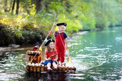 Kids playing pirate adventure on wooden raft royalty free stock images