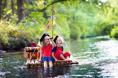Kids playing pirate adventure on wooden raft. Kids dressed in pirate costumes and hats with treasure chest, spyglasses, and swords playing on wooden raft sailing royalty free stock photography