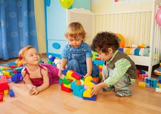 Kids playing with plastic blocks Stock Images