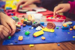 Creativeness with play dough. Kids playing with play dough on the table and creating a snail animal stock photography