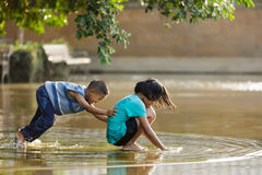 Kids playing in a puddle Royalty Free Stock Images