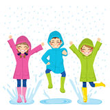 Kids Playing On Puddles. Little kids playing on puddles wearing colorful raincoats and boots Stock Photography