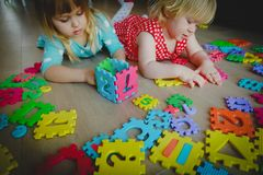 Kids playing with puzzle, learning shapes and numbers. Education stock image