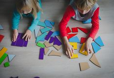 Kids playing with puzzle or tangram, education concept. Kids playing with puzzle or tangram, education and learning concept stock photos